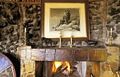 Natural stone wall with a fireplace and crackling fire with animal figurines on the mantelpiece