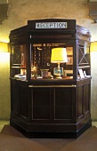 Antique hotel reception desk with a table lamp