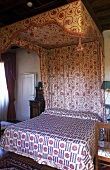 Bedroom in a country home -- canopy bed with floral pattern