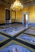 Brass chandelier in a castle's hall with painted stone floor and gold walls