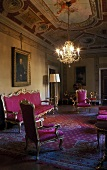 Rococo style sofa and chairs upholstered in red in the living room of a castle with a chandelier hanging from a frescoed ceiling
