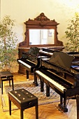 Two pianos with a piano bench in a music room