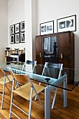 Glass top table on a bright blue metal frame and a honey colored wood floor in a dining room