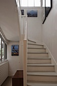 Looking up a country style stairway with white treads and railing