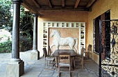 Loggia of a country home with black columns and antique wooden patio furniture in front of a horse in white relief