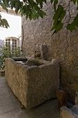 Rustic stone trough with water in front of a natural stone wall and a waterspout