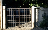 Garden gate made of gray metal grillwork