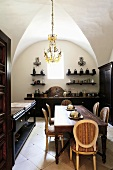 A vaulted ceiling in a dining room with dark wooden furniture and a chandelier