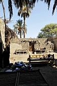 Bänke auf Sandboden im Innenhof mit Lehmmauern und hochgewachsenen Palmen, Ägypten