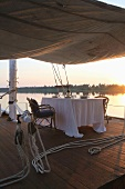 A romantic evening on the river -- table set for tow on the covered sun deck of a boat