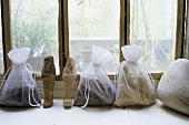 Filled and tied plastic bags on a window sill and small stone figurines