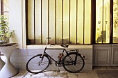 Bicycle parked in a passageway in front of an opaque window