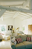 Living room with a sofa and red and white cushions in a converted attic with rustic white wood construction ceiling