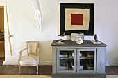 Vintage style gray cabinet with wire mesh doors and white Rococo chairs in an anteroom