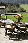 A table laid on a terrace with a colourful bunch of flowers