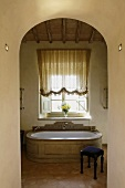 View through an archway of an elegant antique bathtub clad in stone and a stool upholstered in blue