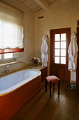 Country style bathroom -- bathtub clad in wood in front of a window with a Roman blind and upholstered stool on a wooden floor