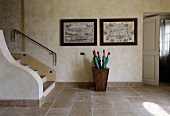 Cool foyer with stairs and umbrella stand in front of copperplate etchings on a wall and a stone floor