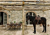 A saddled on the terrace of a country home and a table with chairs under a pergola