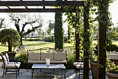 Elegant metal patio furniture upholstered in bright fabric under a pergola with a garden view