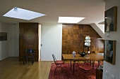 Open living room with skylights and dining area in front of a wood paneled wall