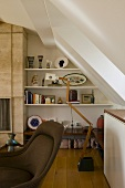 Sloping ceiling with built-in shelves and a floor lamp