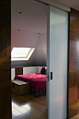 Half open sliding door with a view of a bed and a skylight