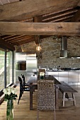 Renovated country home - dining area under a rustic wooden beam ceiling and stainless steel kitchen in front of a natural stone wall