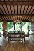 Renovated country home - dining area under a beam ceiling with a designer pendant lamp in front of terrace windows