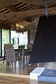 Open fireplace with a black flue and raised dining area under a wooden beam ceiling