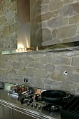 Stainless steel kitchen countertop with integrated stove and extractor fan in front of a natural stone wall