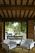 Renovated country home - two white designer style armchairs in front of a terrace window with a view