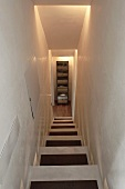 Looking down a narrow stairwell with indirect lighting at a cupboard at the bottom of the stairs