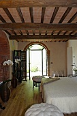 Elegant bedroom in a renovated country home with a rustic wooden beam ceiling and open terrace doors in a round arch