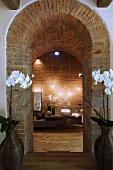 View through a brick arch of bathroom furnishings with atmospheric lighting