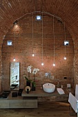 Designer style vanity with improvised lighting made of hanging light bulbs in front of a brick wall and barrel ceiling