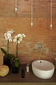 Vanity with a ceramic sink in front of a brick wall and white orchids in a vase