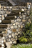 Overhanging stairs made of block of stone on a natural stone wall