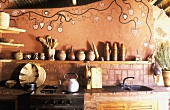 A rustic, African-style kitchen with a painted wall