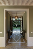 An open hallway in a villa with a terrazzo floor and view of the garden