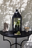 Lantern and ceramics on a black console table in front of a white house facade