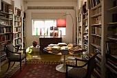 Bibliothek mit weissen Einbauregalen und antiken Stühlen