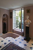 Pink anteroom with a tiled floor and busts next to a stair entrance and open window