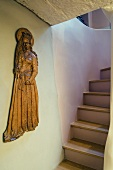 Wooden Madonna on a wall in front of a flight of stairs