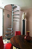 Wooden table with red chairs in front of metal spiral staircase with a spindle