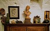 Holzbüste und Antiquitäten auf einem Holzschränkchen vor rustikaler Wand