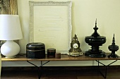 Still life on a wooden table top - white table lamp, a set of brown canisters, Rococo clock and black Asian containers