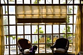 Sunny day - wicker chairs in front of lattice windows with a view of a terrace and the ocean