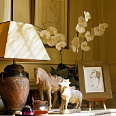 A table lamp with a white shade and stone animal figures on a shelf