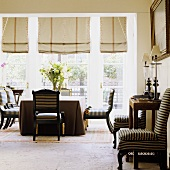 An elegant living room in a villa - black antique chairs with striped covers in front of floor-to-ceiling windows with Roman blinds